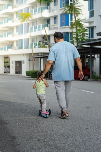 Father walking with girl riding push scooter on road in city