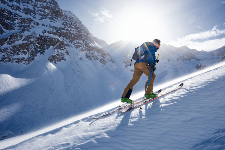 Full length of man skiing on snowcapped mountains during winter