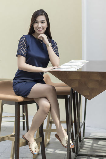 Portrait Of Smiling Young Woman Sitting At Table In Restaurant