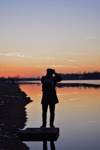 Rear View Of Silhouette Man Standing Over Lake Against Sky During Sunset