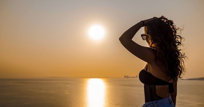 EyeEm Selects Sunset Sea Beach Sun Horizon Over Water Beauty In Nature One Person Long Hair Vacations Nature Idyllic Sky Standing Scenics Water Sand Tranquility Tranquil Scene Sunlight One Woman Only