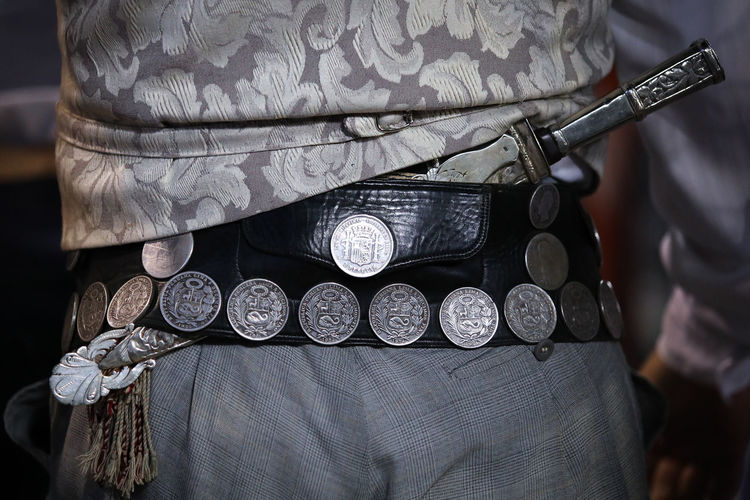 Midsection of man wearing antique belt with knife