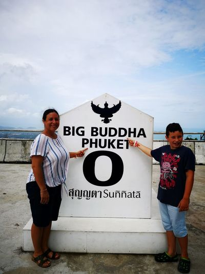 Portrait of mother and son pointing at sign against cloudy sky