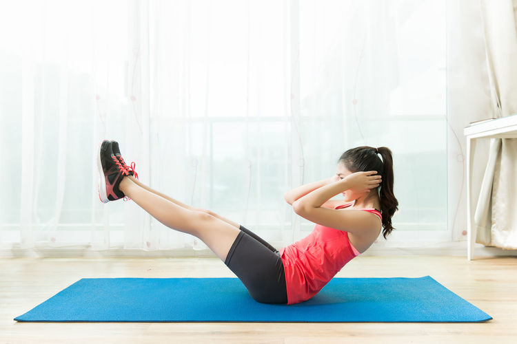 Adult Beautiful Woman Clothing Exercise Mat Exercising Flexibility Full Length Hairstyle Healthy Lifestyle Indoors  Lifestyles One Person Physical Activity Real People Relaxation Exercise Sport Stretching Wellbeing Women Yoga Young Adult Young Women
