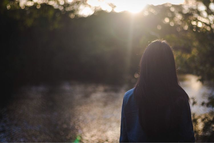 Rear view of woman standing at riverbank during sunset