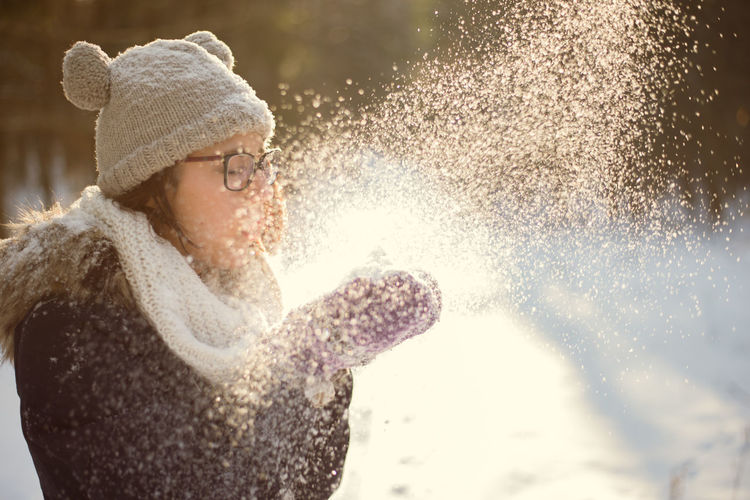 Beauty In Nature Close-up Cold Temperature Day Enjoyment Focus On Foreground Fun Happiness Leisure Activity Lifestyles Motion Nature One Person Outdoors People Real People Snow Splashing Spraying Sunlight Warm Clothing Water Winter Young Adult Young Women