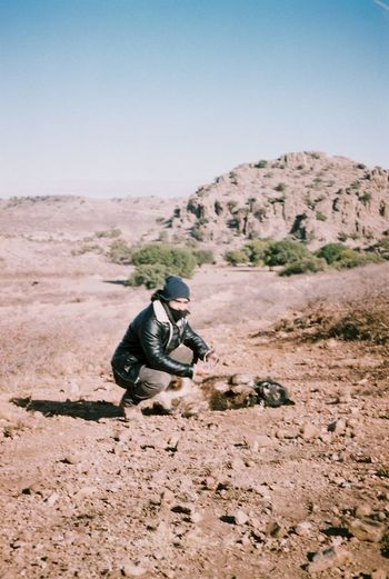 Man on rock in desert against clear sky