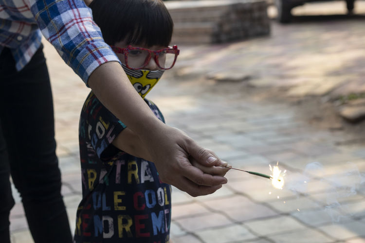 Midsection of mother and son holding sparkler while standing outdoors