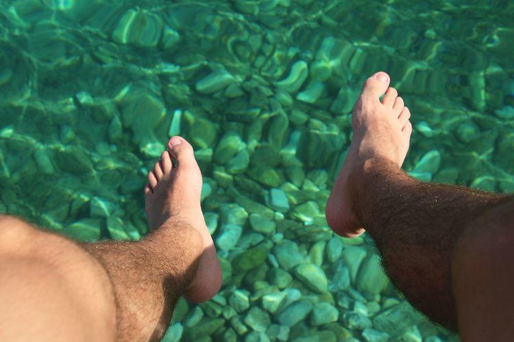 Feet dangling over emerald sea waters.