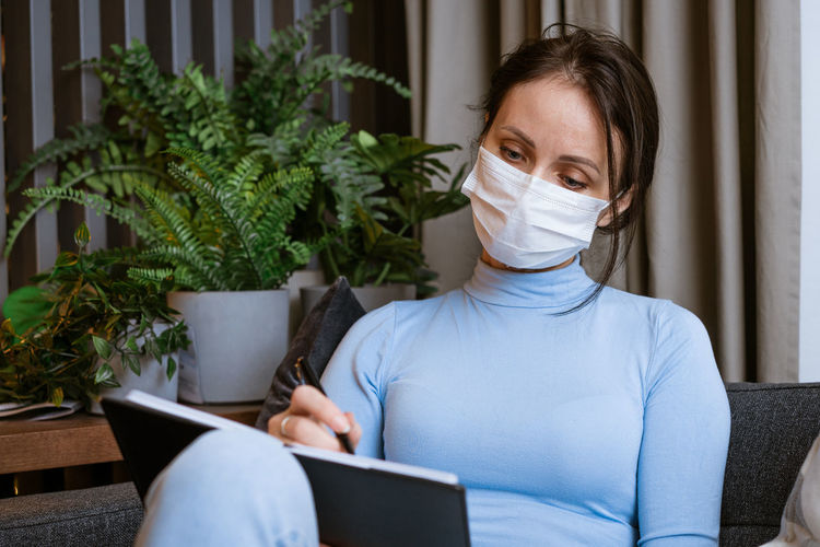 Woman in protective mask on the couch with notepad in hand