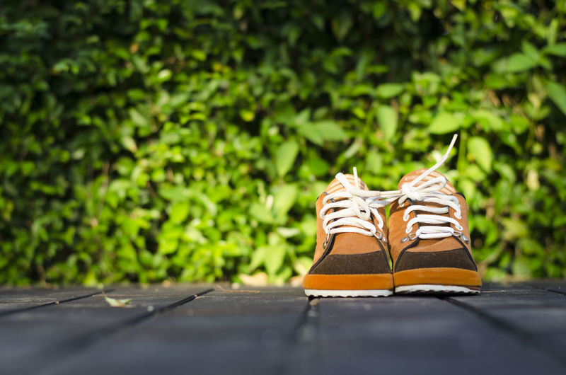 Children brown shoes on a floor with leaves background in sunny evening. wear brown shoes day