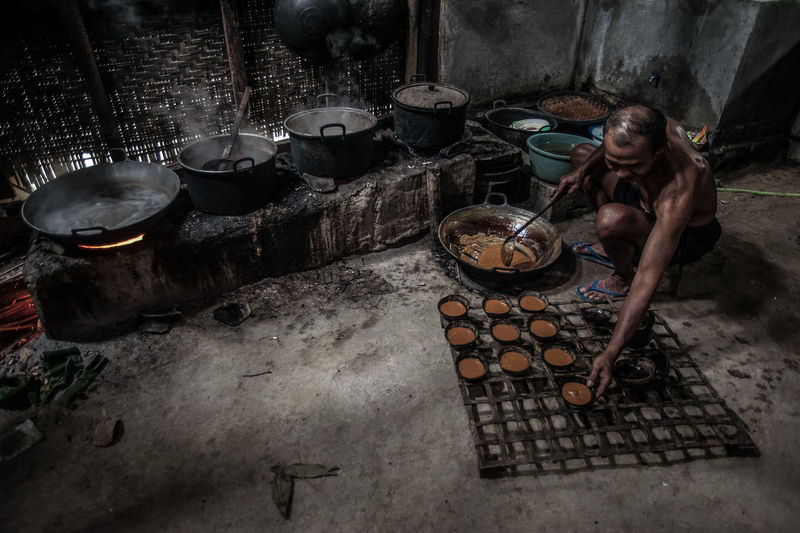 Shirtless man serving food in bowls by wood burning stove in kitchen