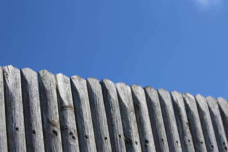 Low Angle View Of Wooden Fence Against Clear Blue Sky