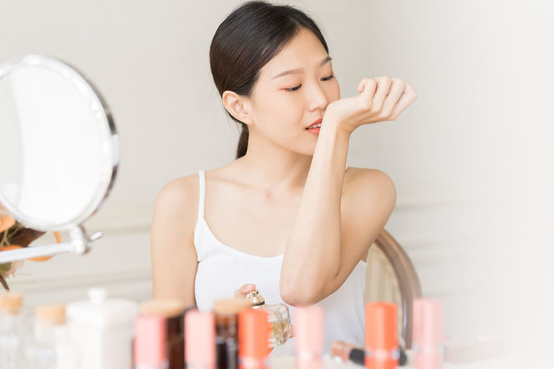 Young woman smelling perfume at home