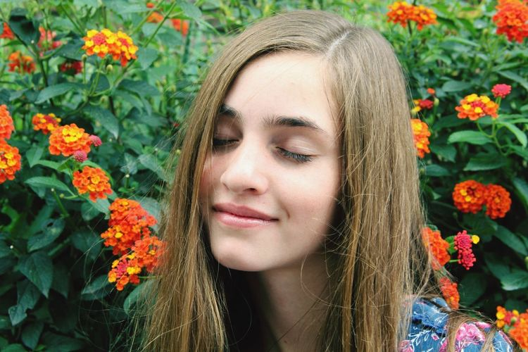 Close-up of young woman with eyes closed by lantana camara
