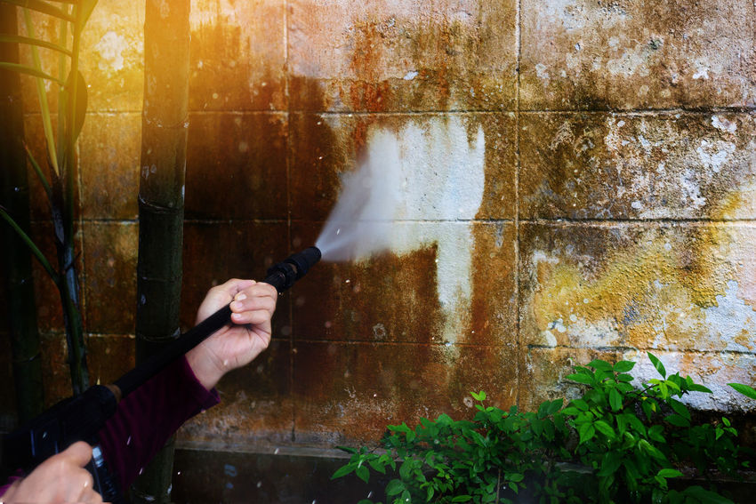 High pressure cleaning,back view. Man cleaning old dirty grunge wall with high pressure water jet ,professional cleaning services selective focused. Dirty Wall Man Spraying Spraying Water Grunge Wall Hand High Pressure Cleaner Outdoor Water Water Jet Wet