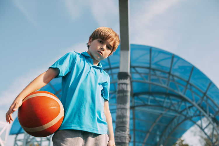 Low angle portrait of boy with basketball standing against sky