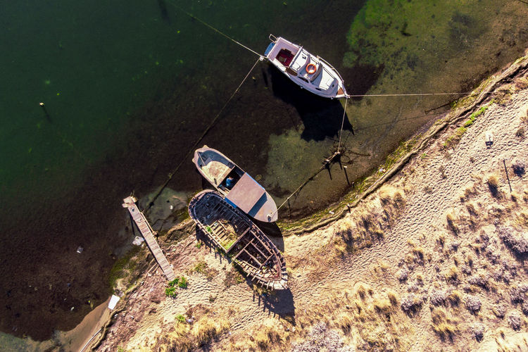 An aerial view of the boat that attached to the beach. Transportation Mode Of Transportation High Angle View Day Nature Nautical Vessel Water No People Outdoors Land Plant Land Vehicle Abandoned Beach Dirt Sunlight Tranquility Travel Moored Mud Sinking Ruined Dronephotography Top View Aerial View
