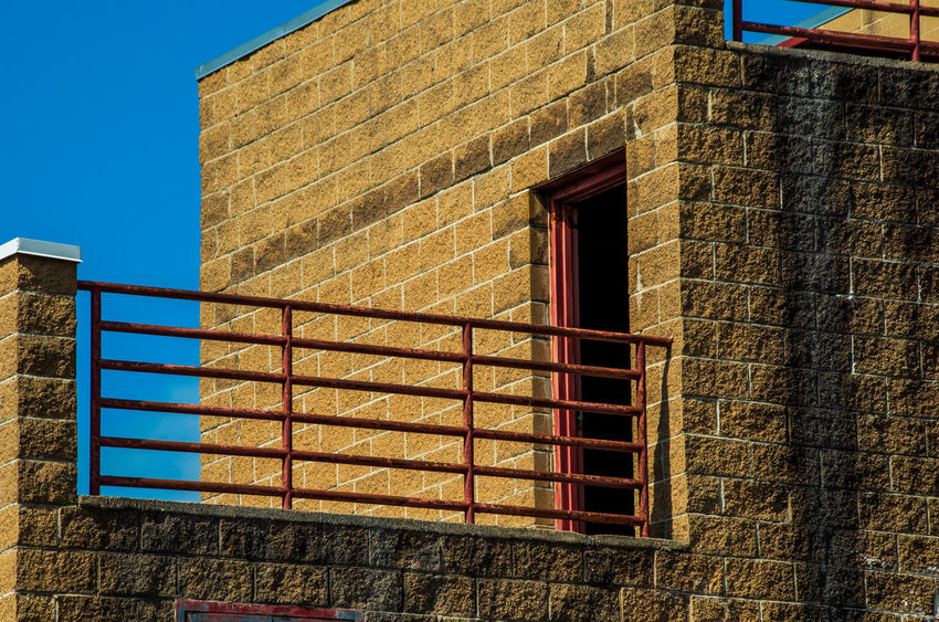 Architecture Blue Brick Brick Wall Building Building Exterior Built Structure Clear Sky Day Low Angle View Nature No People Outdoors Railing Residential District Sky Sunlight Wall Wall - Building Feature Window