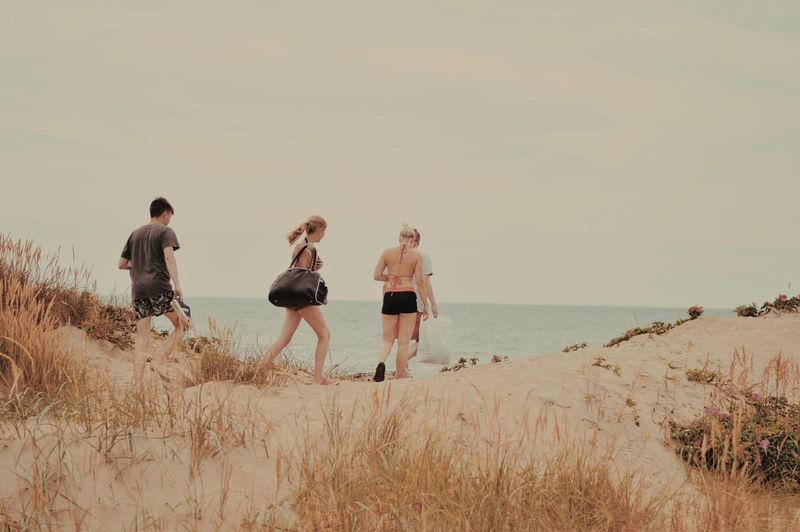 Friends walking on beach against sky