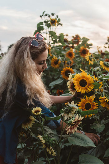 Portrait of young woman with sunflower amidst plants
