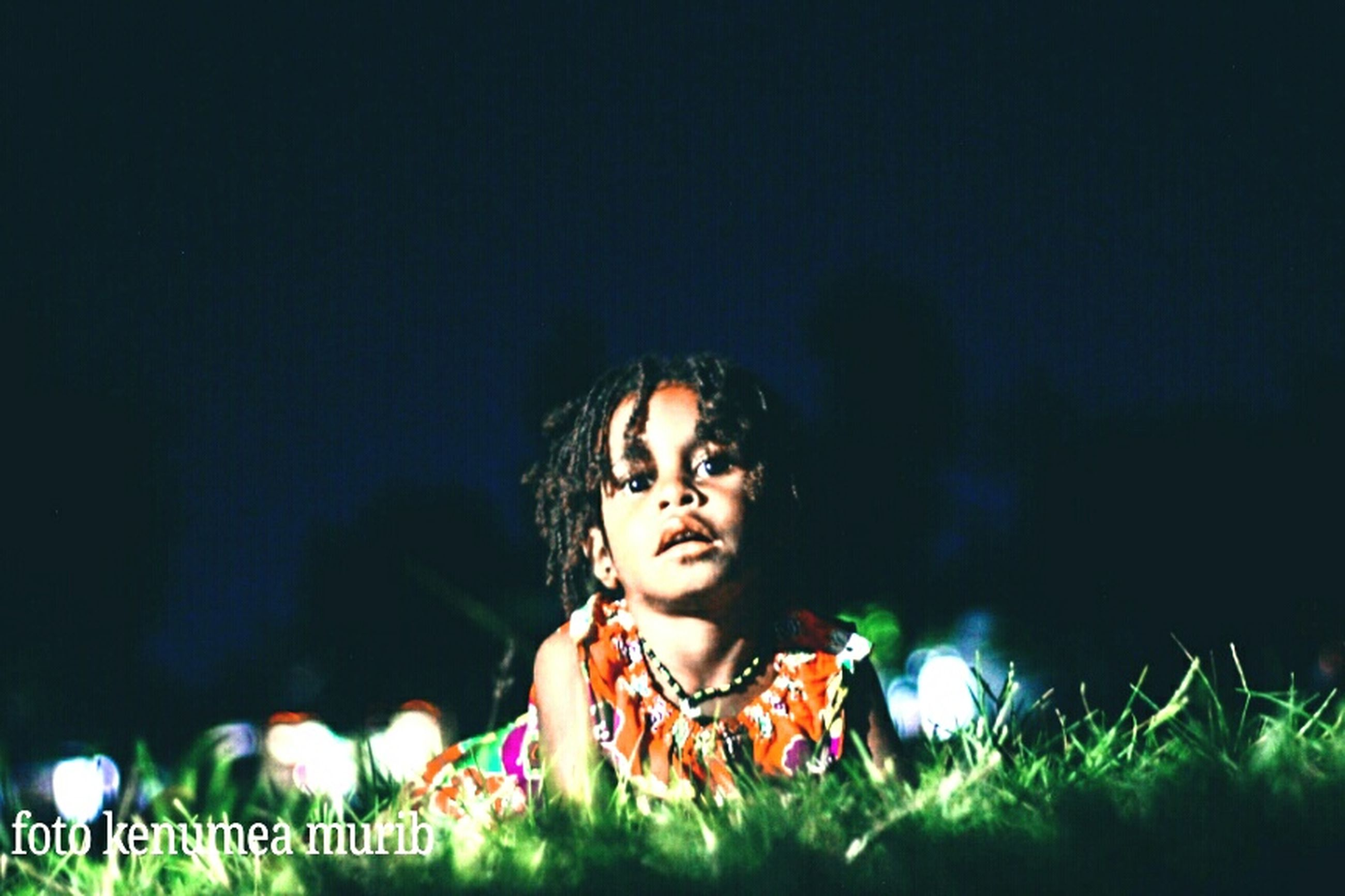 one person, night, child, looking, headshot, portrait, childhood, grass, front view, real people, lifestyles, leisure activity, illuminated, innocence, casual clothing, copy space, women, nature, dark, hairstyle, contemplation