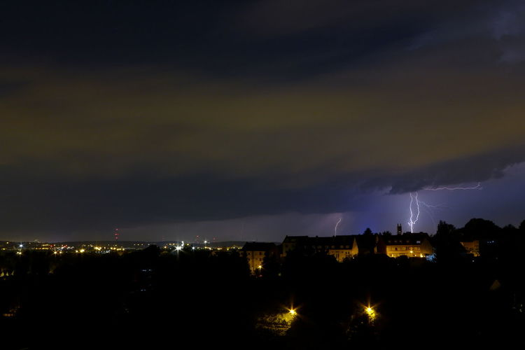 Lightning over illuminated city at night