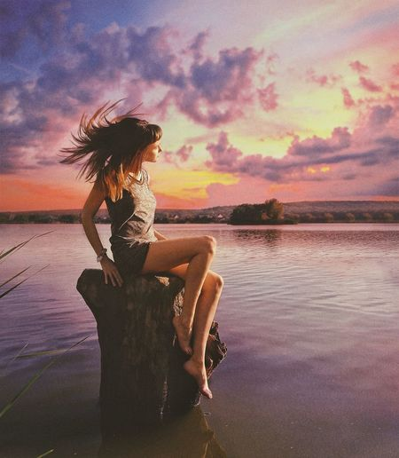 Woman sitting by lake against sky during sunset