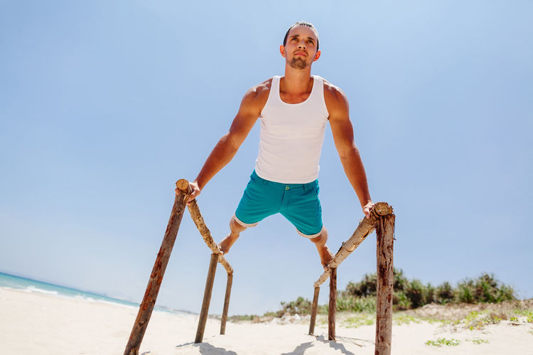 Man training and workout on beach. Fitness outdoors. Beach One Person Sand Sea Ocean Fitness Fitness Training Outdoors Man Males  Strong Yoga Stretching Workout Sport Leisure Activity Lifestyles Relaxing Exercising