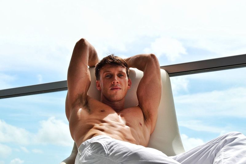 Portrait of shirtless young man reclining on chair by glass railing in balcony against sky