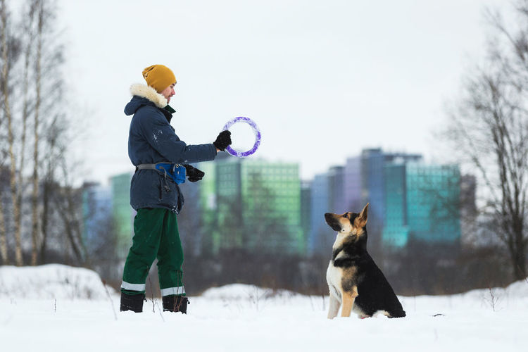Man playing with dog in snow against sky