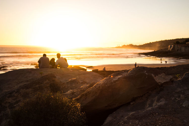 Friends Sitting On Rock Against Sea During Sunset