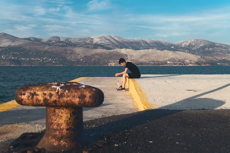 Man looking at sea against mountain