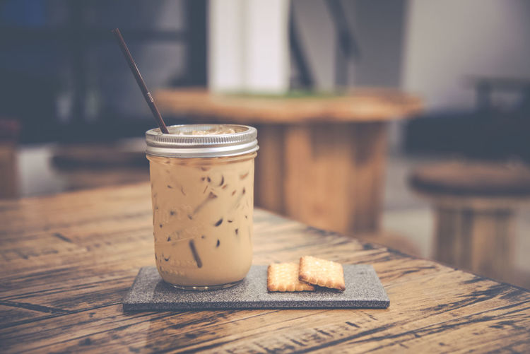 Iced Coffee And Cracker Served On Wooden Table