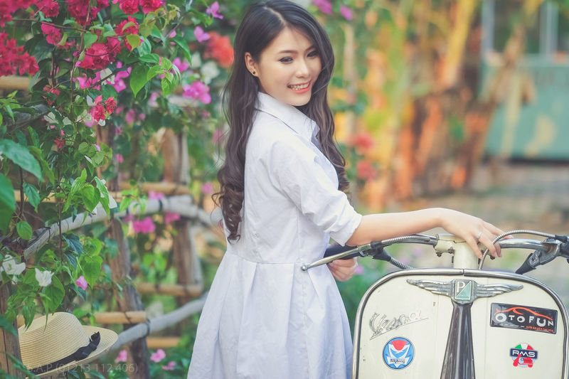 Side View Of Smiling Young Woman Standing By Motor Scooter