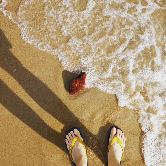 Waves Breaking On A Shore Slippers At The Beach Feet In The Sand Dried Fruit Floating On The Beach One Person Beach Outdoors