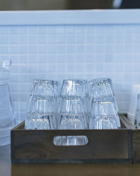 Stacked empty glasses in wooden tray on kitchen counter