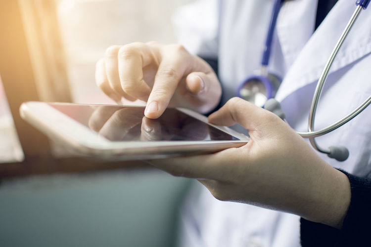 Midsection Of Doctor Using Phone