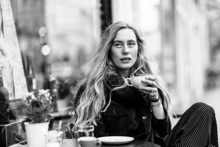 Portrait of woman holding coffee cup while sitting at table