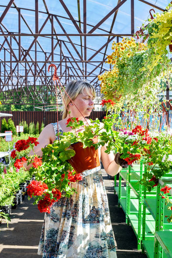 Woman holding flowers in greenhouse