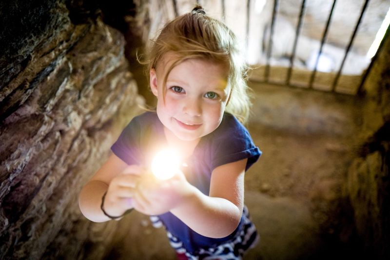 Looking At Camera Portrait Blond Hair Holding Casual Clothing One Person Child Sunlight Outdoors Sunbeam Smiling Happiness People Nature Day Young Girl Close-up Human Hand Flashlight Cave EyeEm Best Shots