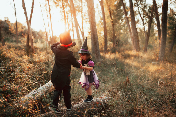 Girl wearing witch hat standing with brother at forest during halloween