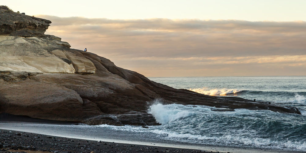 A person sitting on rocks looking out to sea.