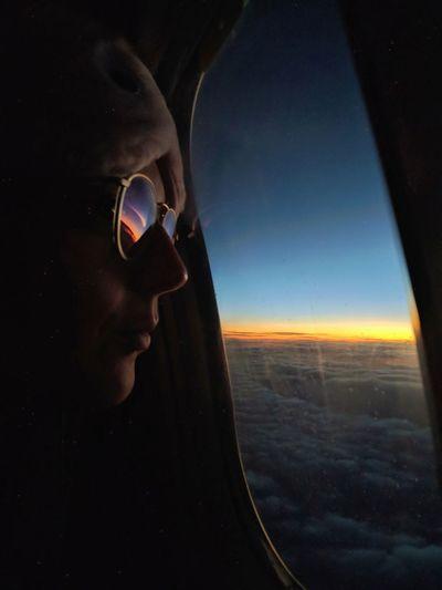 Man looking through airplane window against sky