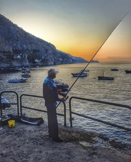 Fishing at dawn Fishing One Person Real People Water Standing Full Length Fishing Pole Sea Leisure Activity Tranquil Scene Nature Side View Beauty In Nature Tranquility Holding Scenics Outdoors Lifestyles Sky Men