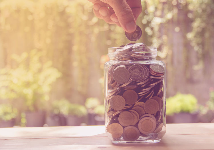 Cropped hand of man putting coins in jar on table