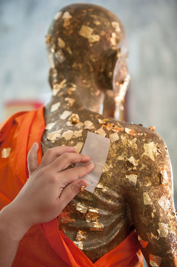Cropped hand of person touching statue with paper