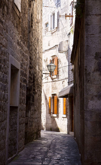 Narrow cobbled street in Trogir center, antique Dalmatian city founded 4000 years ago. Ancient Architecture Building Exterior Built Structure Cobblestone Croatia Day Historical Medieval Narrow Street No People Old Town Outdoors Shadow Southern Europe Stone Street Lamp Sunlight Travel Destination Trogir