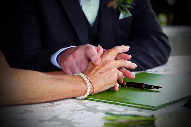 Adult Bonding Bride Bridegroom Ceremony Close-up Day Holding Human Body Part Human Hand Indoors  Love Love Marriage  Midsection Real People Register Registration Senior Men Togetherness Two People Wedding Wedding