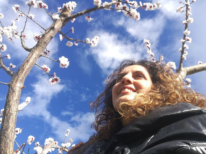 Low Angle View Leisure Activity Lifestyles Sky Headshot Tree One Person Nature Women Young Women Smiling Portrait Young Adult Plant Real People Happiness Sunlight Day Warm Clothing Outdoors Hairstyle Springtime Cherry Blossoms